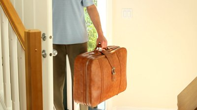 stock-footage-business-man-returning-home-from-travel-carrying-a-suitcase-and-climbing-stairs-after-closing-the